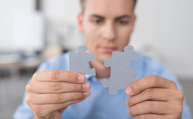 Student hält 2 pasasende Puzzleteile aneinander