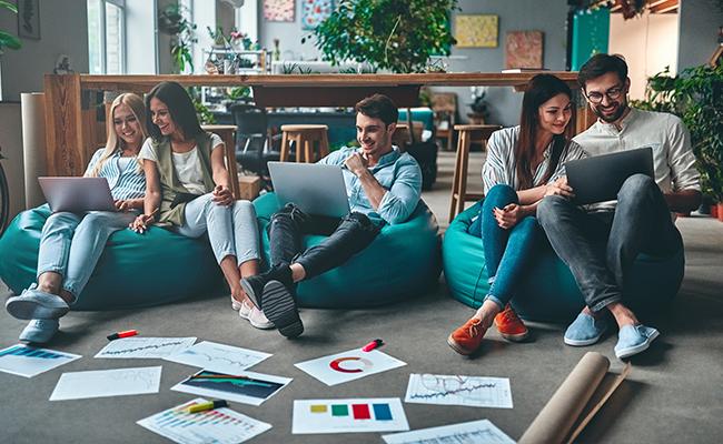Schüler sitzen am Boden und arbeiten an Arbeitsmaterial